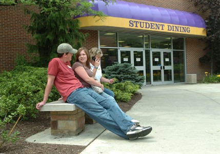 Two people sitting on a bench outside of the student dining building