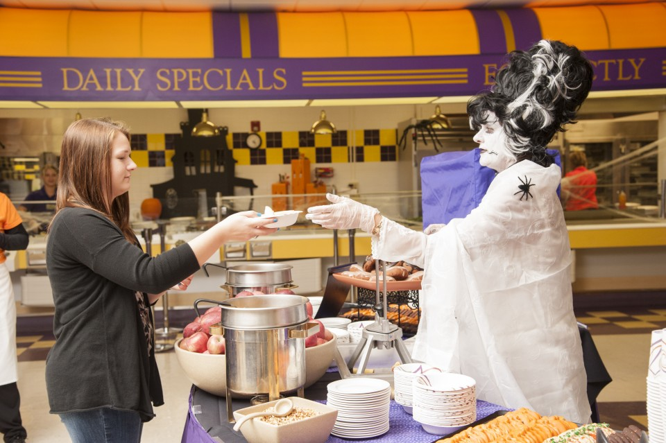 Student being served her food by someone dressed like a ghost