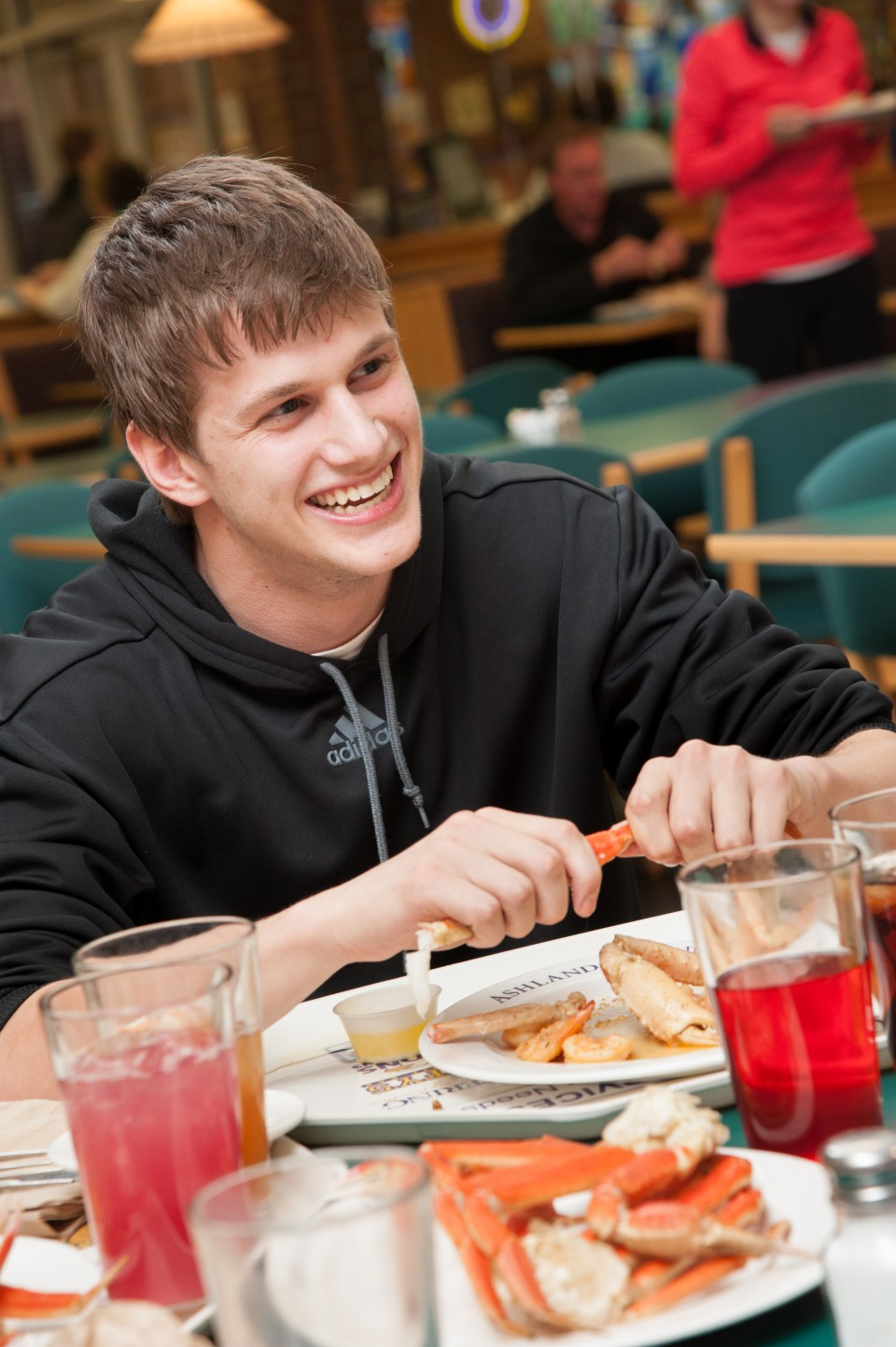 Student eating Crab Legs at a table inside Student Dining