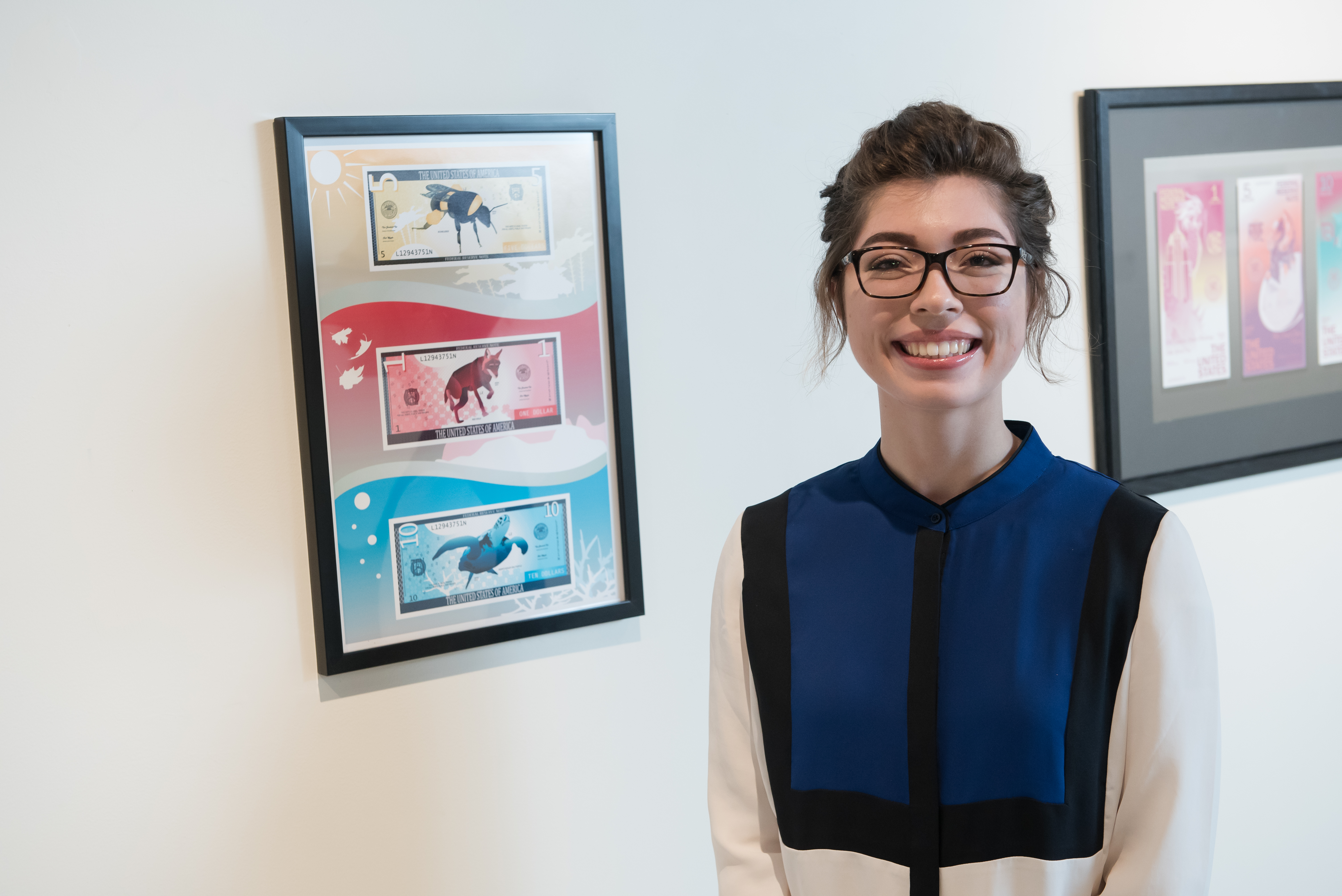 student posing with artwork