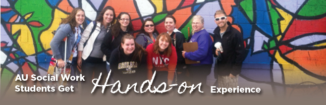 Social Work students pose in front of a colorful wall
