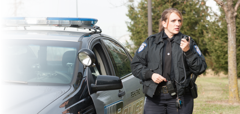 Female police officer standing beside car