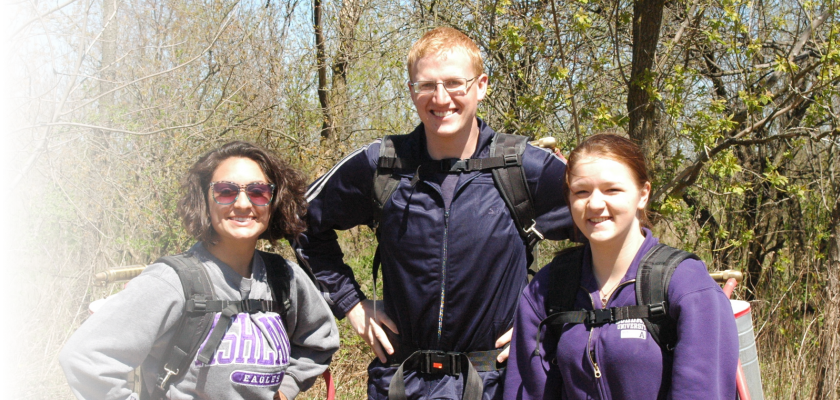 3 Students Outside in the woods with backpacks on