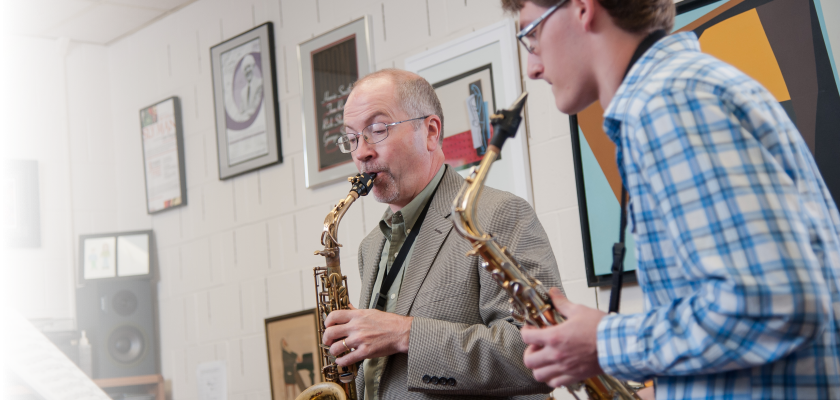 Student and professor playing the saxophone