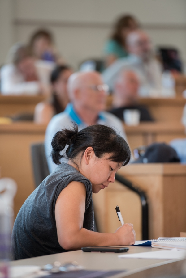 Woman focused on her writing at a table with other writers listening to a presenter behind her.