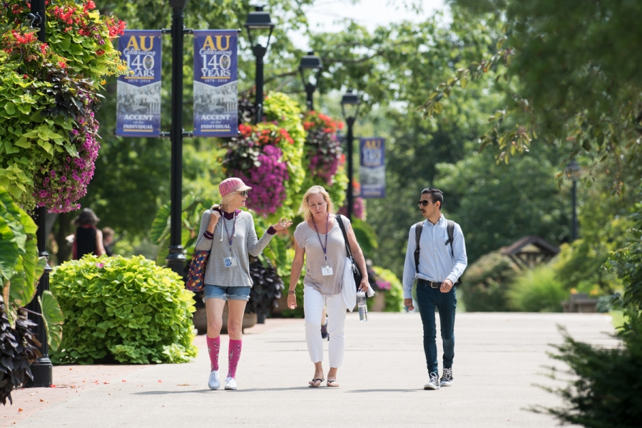 Faculty and students walking outside in summer.