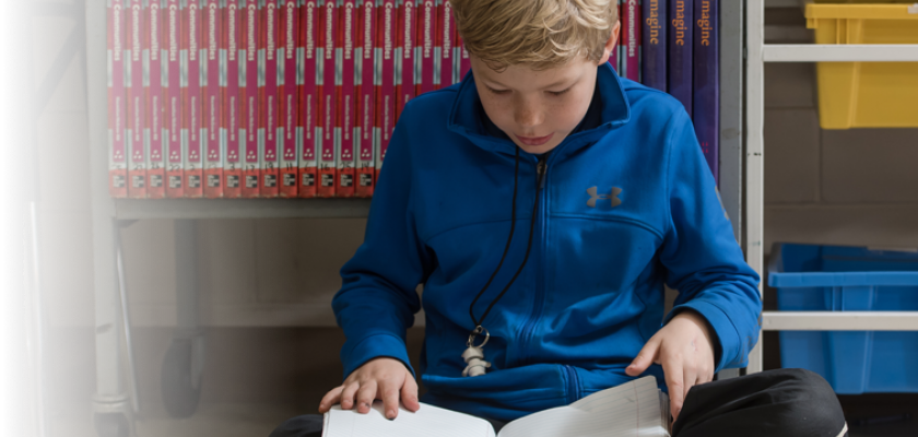 Middle Schooler looking at book leaning against a shelf