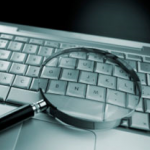 Photo of a laptop computer and a magnifying glass