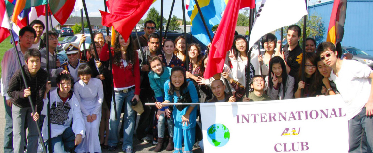 Group of International Students holding an Ashland University International Club Banner