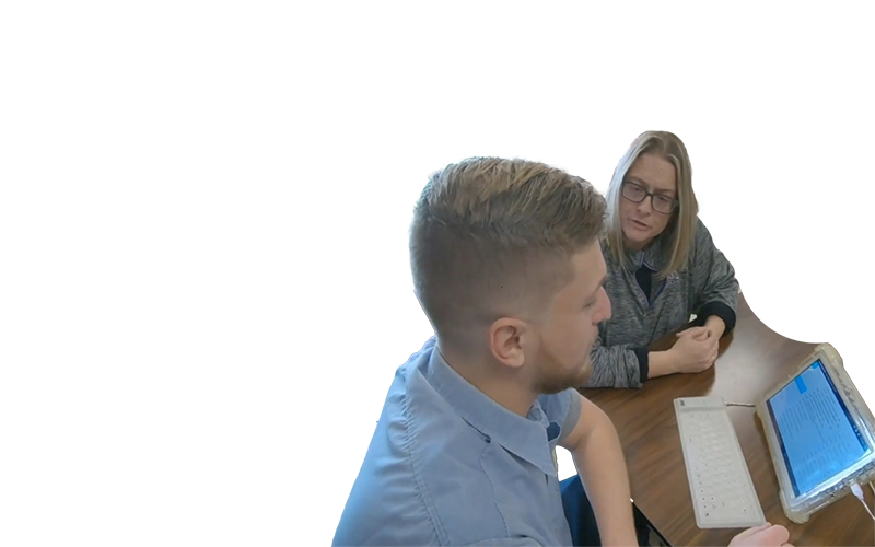 student sitting at a tablet with a teacher